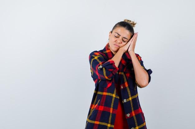 Mulher loira com camisa quadriculada, apoiando-se na palma da mão como travesseiro e parecendo cansada, vista frontal.