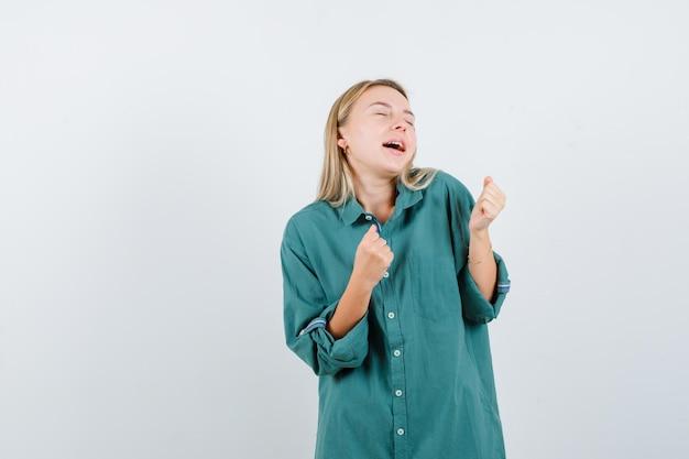 Mulher loira com camisa verde mostrando gesto de vencedor e parecendo feliz