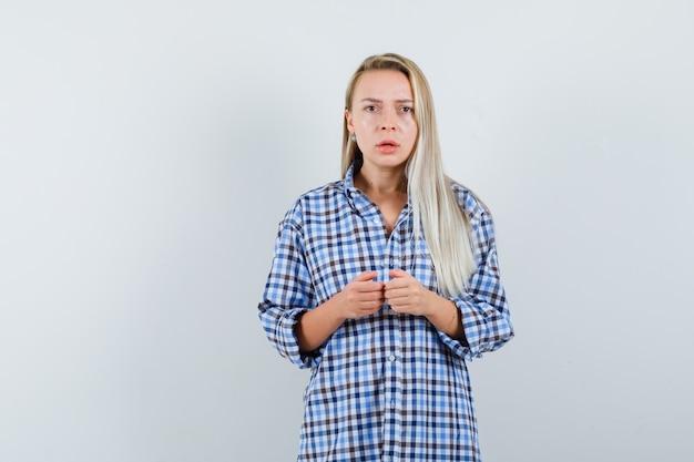Mulher loira com camisa xadrez azul guingão de mãos dadas enquanto joga o console e parecendo aflita, vista frontal.