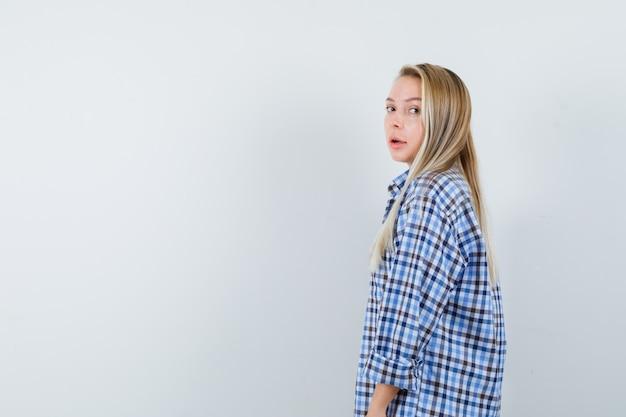 Mulher loira com camisa xadrez azul guingão em pé em linha reta e posando para a câmera e olhando encantador, vista frontal.