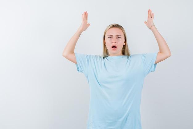 Mulher loira com camiseta azul levantando as mãos acima da cabeça segurando algo pesado