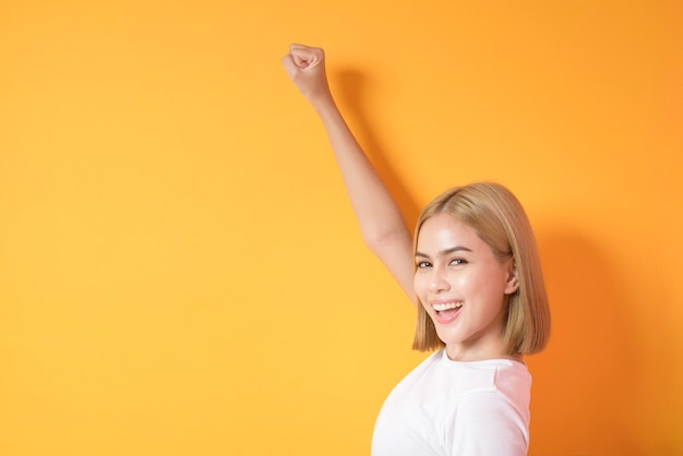 Mulher loira com camiseta branca posando em laranja