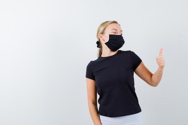Mulher loira com camiseta preta, calça branca, máscara preta aparecendo com o polegar