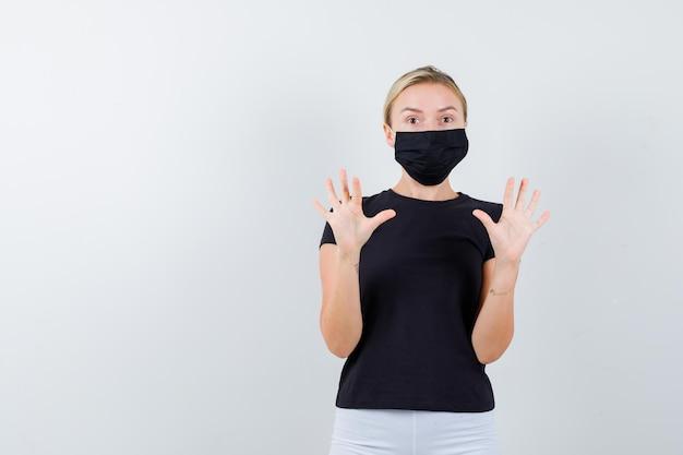 Mulher loira com camiseta preta, calça branca, máscara preta levantando as palmas das mãos