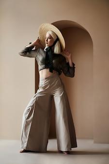 Mulher loira com chapéu de palha em pé perto da parede com os pés descalços