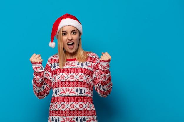 Mulher loira com chapéu de papai noel gritando agressivamente com uma expressão de raiva ou com os punhos cerrados celebrando o sucesso