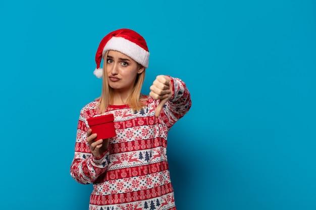 Mulher loira com chapéu de papai noel se sentindo zangada, irritada, decepcionada ou descontente, mostrando o polegar para baixo com um olhar sério