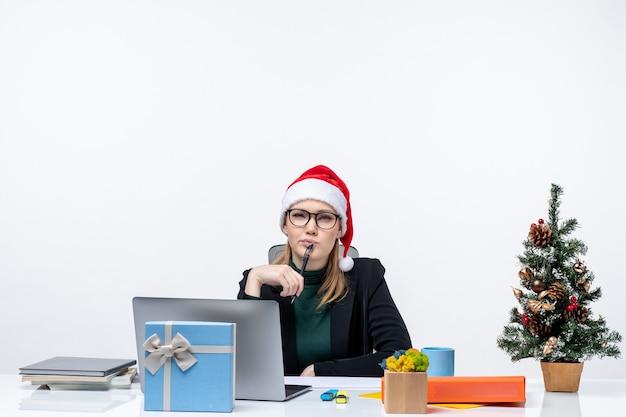 Mulher loira com chapéu de papai noel sentada à mesa com uma árvore de natal e um presente