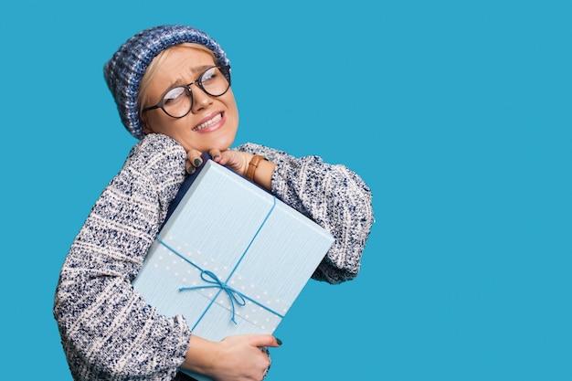 Mulher loira com chapéu e óculos está abraçando fortemente um presente enquanto promove algo em uma parede azul