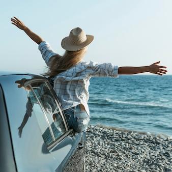 Mulher loira com chapéu em pé na janela do carro