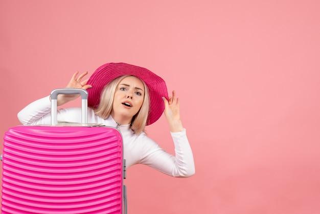 Mulher loira com chapéu-panamá rosa em pé atrás da mala
