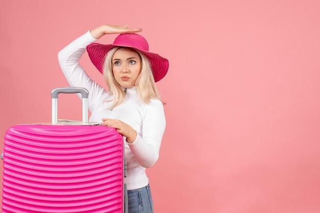Mulher loira com chapéu-panamá rosa segurando a mala de frente