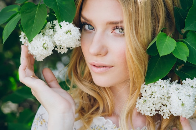 Mulher loira com flores lilás na primavera