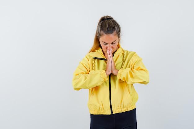 Mulher loira com jaqueta militar amarela e calça preta em pose de oração e olhando focada