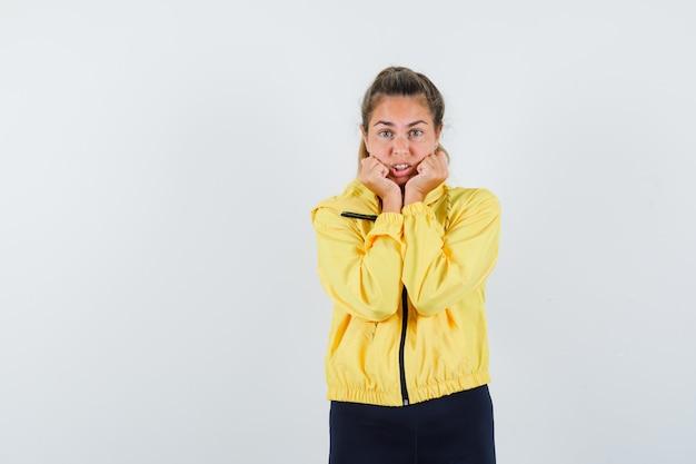 Mulher loira com jaqueta militar amarela e calça preta segurando as mãos no rosto, cerrando os punhos e parecendo animada