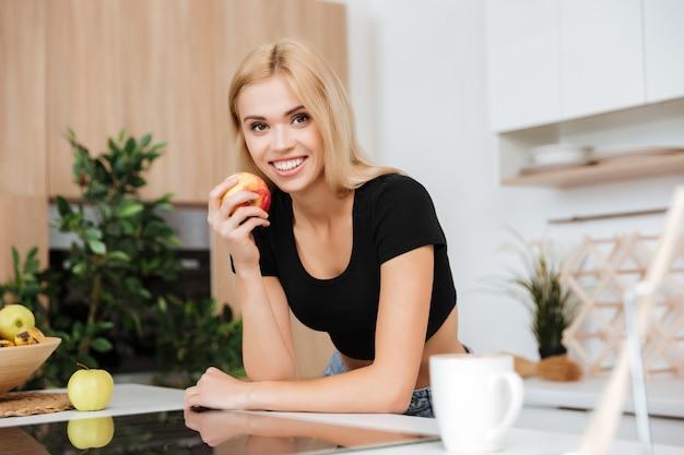 Mulher loira com maçã na cozinha