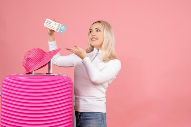 Mulher loira com mala rosa e chapéu panamá segurando o ingresso