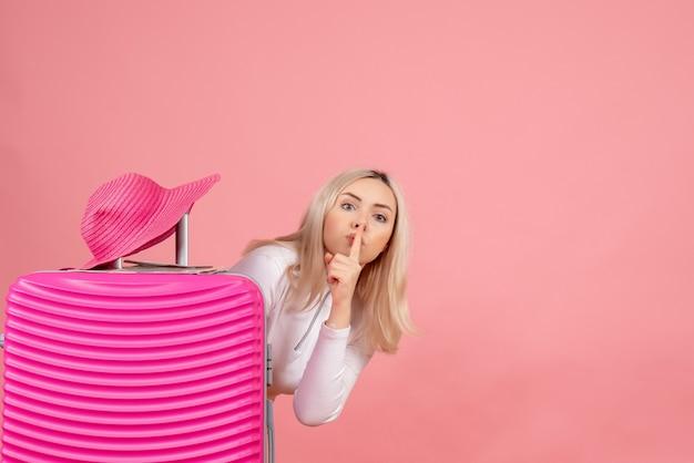 Mulher loira com mala rosa fazendo sinal de silêncio e chapéu-panamá de frente