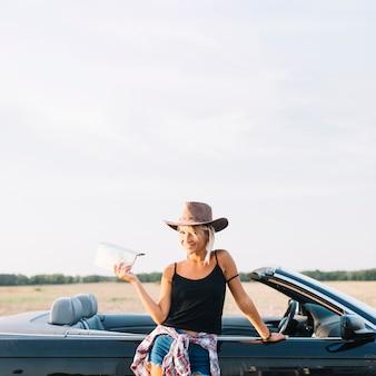 Mulher loira com mapa perto de cabriolet