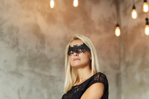 Mulher loira com máscara em forma de morcego para o halloween ou festa de máscaras e traje preto