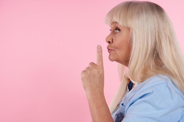 Mulher loira com o dedo indicador no lábios mostra sinal mais silencioso.