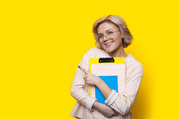 Mulher loira com óculos apontando para um espaço livre amarelo enquanto segura alguns livros