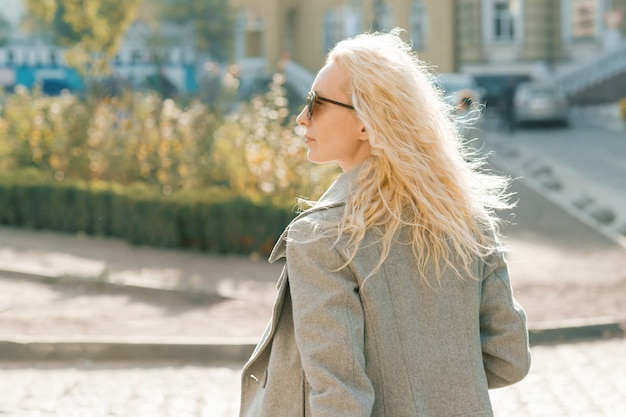 Mulher loira com óculos de sol com cabelo longo cacheado