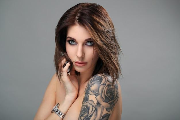 Mulher loira com olhos esfumaçados e com tatuagem