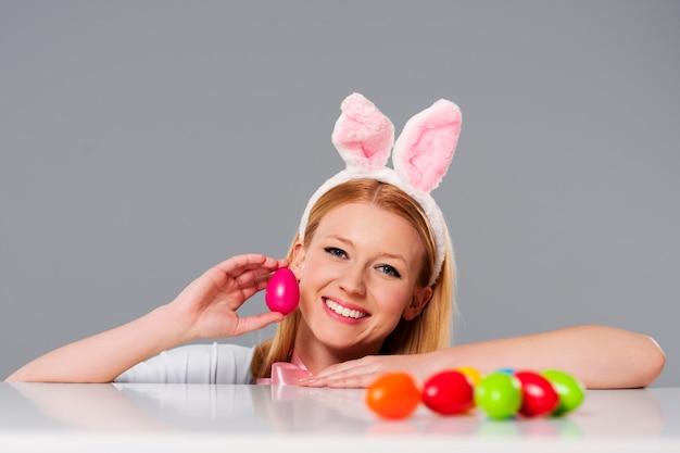 Mulher loira com orelhas de coelho e ovos de páscoa