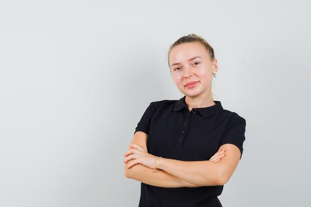 Mulher loira com os braços cruzados e sorrindo em uma camiseta preta