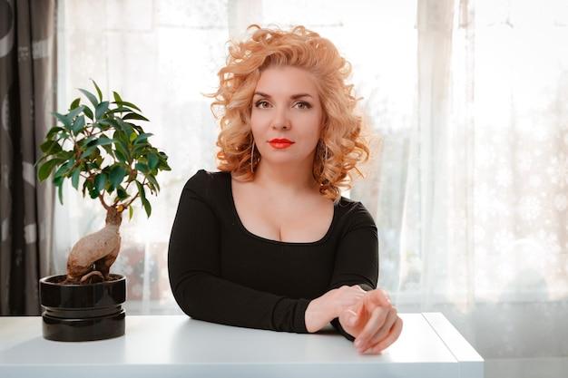 Mulher loira com penteado retrô e lábios vermelhos brilhantes posando em casa