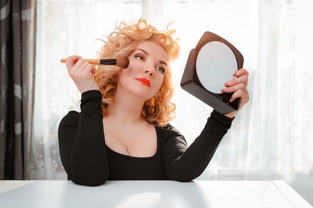 Mulher loira com penteado retrô e lábios vermelhos brilhantes usando pincel de maquiagem