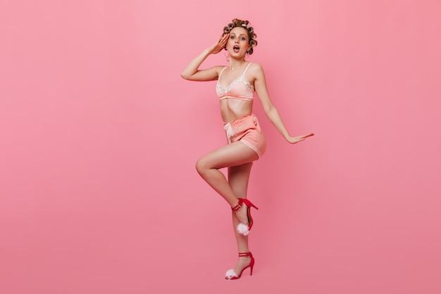 Mulher loira com pijama pin-up saudando a parede rosa