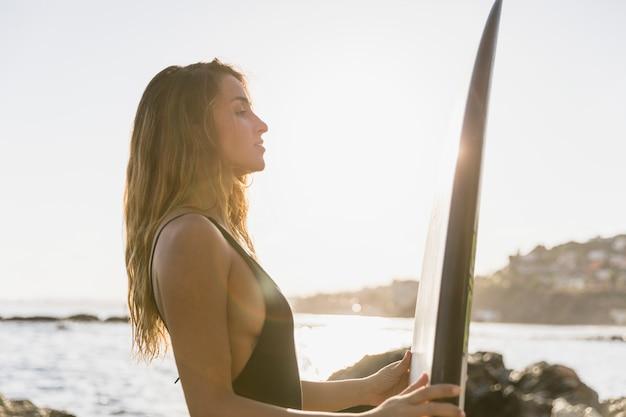 Mulher loira com prancha de surf na costa do mar