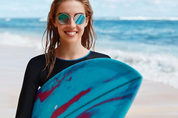 Mulher loira com prancha de surf na praia