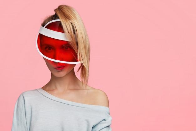 Mulher loira com rabo de cavalo e chapéu vermelho da moda