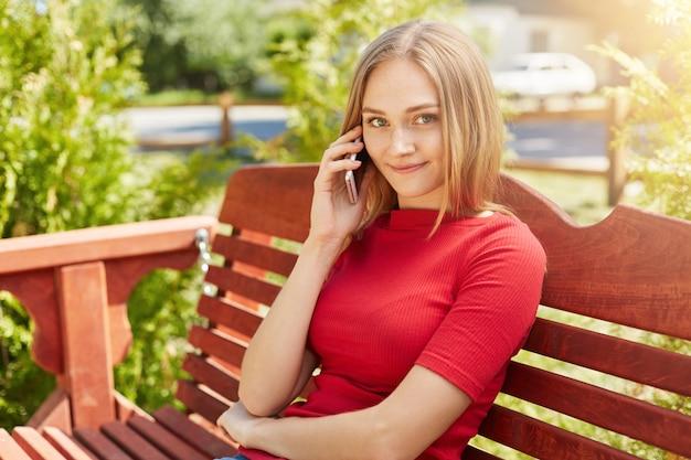 Mulher loira com sardas tendo sorriso gentil enquanto está sentado no banco confortável de madeira no parque