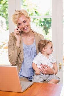 Mulher loira com seu filho usando telefone e laptop