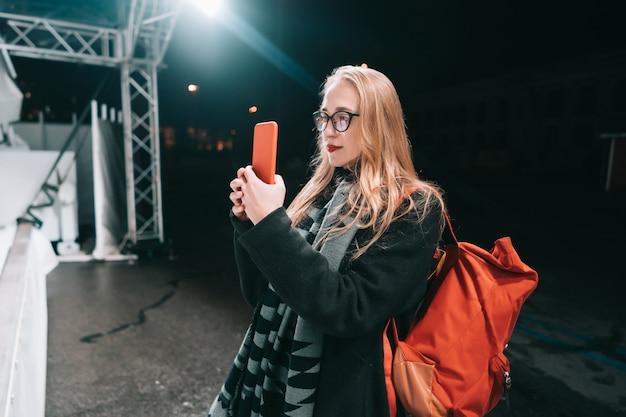 Mulher loira com smartphone à noite na rua.