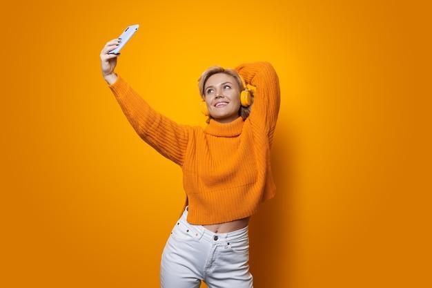 Mulher loira com suéter amarelo usando fones de ouvido fazendo uma selfie na parede