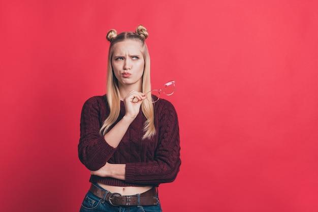 Mulher loira com topete e óculos posando contra a parede vermelha