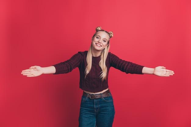 Mulher loira com topos posando contra a parede vermelha