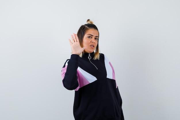Mulher loira com um agasalho de treino preto mostrando um gesto de pare e parecendo pensativa