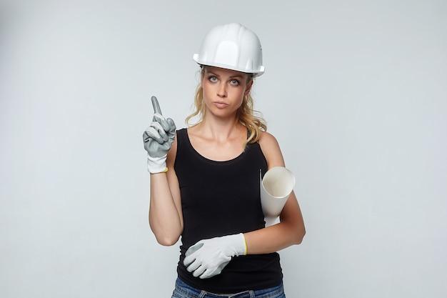 Mulher loira. com um capacete de segurança branco apontando para cima. conceito de construção