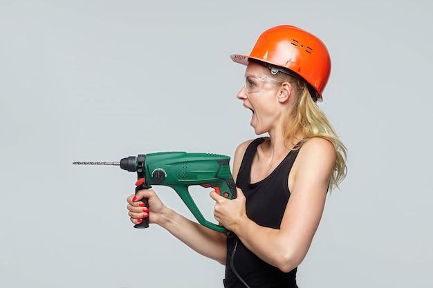 Mulher loira. com um capacete protetor laranja tem uma furadeira nas mãos. conceito de construção