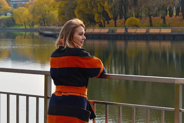 Mulher loira com um casaco de outono fica no passeio.