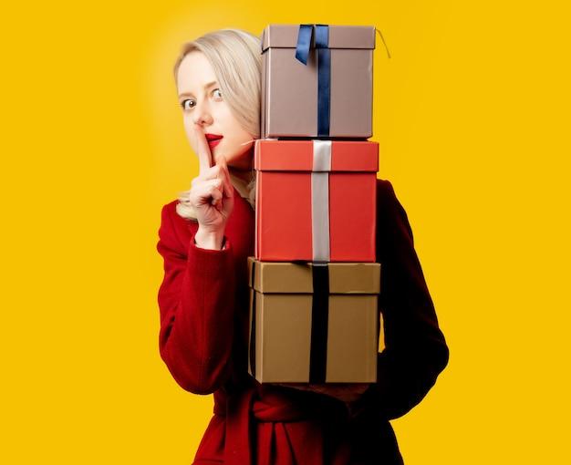 Mulher loira com um casaco vermelho e caixas de presente na parede amarela