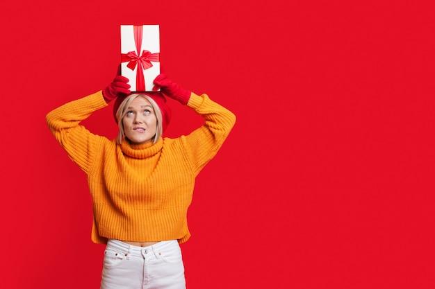 Mulher loira com um chapéu e um suéter quente segurando na cabeça uma caixa de presente enquanto posa na parede vermelha de um estúdio com espaço livre