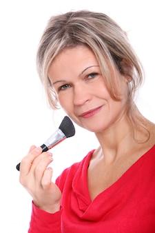 Mulher loira com um pincel de maquiagem