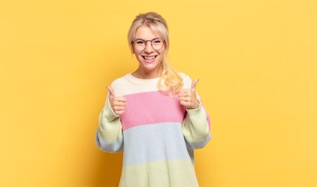Mulher loira com um sorriso largo, parecendo feliz, positiva, confiante e bem-sucedida, com os dois polegares para cima